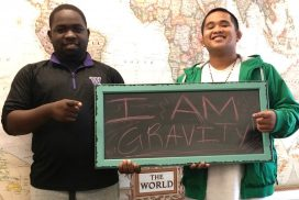"Two students holding ""I am Gravity"" sign"